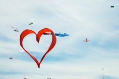 Красный змей формы сердца летает в голубое небо Стоковые Изображения RF