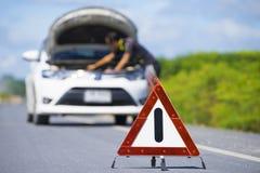 Красный знак аварийного стопа и белый автомобиль после аварии на дороге стоковая фотография