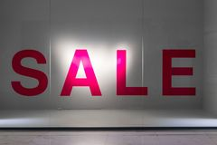 Красный знак продажи на ясной стеклянной витрине против белой стены Стоковое Изображение
