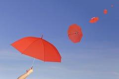Красный зонтик в руке на предпосылке голубого неба Стоковая Фотография RF
