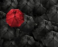Красный зонтик с падением воды стоит вне от толпы много bl стоковые изображения rf