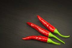 Красный зябкий перец на деревянной черной предпосылке Краснокалильные перцы chili Ожог горячих чилей отечественного культивирован Стоковая Фотография RF