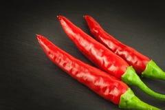 Красный зябкий перец на деревянной черной предпосылке Краснокалильные перцы chili Ожог горячих чилей отечественного культивирован Стоковое Изображение RF