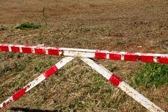 Красный и белый барьер предупредительного знака на зеленой траве в предпосылке природы Переход, регулирование дорожного движения стоковое изображение