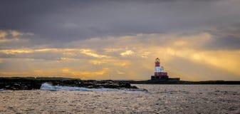 Красный и белый маяк на острове окруженном облаками шторма стоковые фото