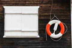 Красный и белый lifebuoy спасательный пояс при веревочки вися от темного коричневого цвета покрасил деревянную стену Стоковое Изображение