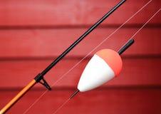 Красный и белый bobber на рыболовной удочке Стоковые Изображения RF