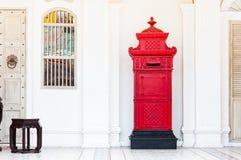 Красный и винтажный postbox перед старым зданием Стоковая Фотография