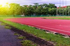 Красный идущий след в стадионе, идущий след на голубом небе в утре Стоковые Изображения