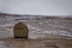 Красный камень с надписью GEYSIR стоит на горячей земле в долине гейзеров в Исландии стоковое фото rf