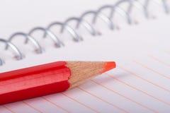 Красный карандаш на тетради Стоковая Фотография RF