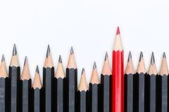Красный карандаш стоя вне от толпы собратьев множества идентичных Стоковое фото RF