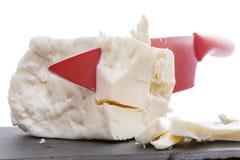 Красный керамический нож отрезая через сыр фета Стоковая Фотография RF