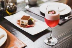 Красный коктеиль в отбензинивании бокала с пеной, цветками и розмариновым маслом Стоковое фото RF
