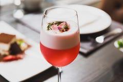 Красный коктеиль в отбензинивании бокала с пеной, цветками и розмариновым маслом Стоковая Фотография RF