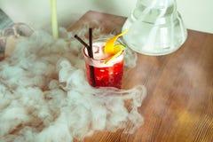 Красный коктеиль на таблице с кусками известки и апельсина Стоковое Фото