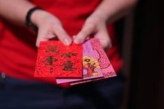 Красный конверт с словами благословением для китайских подарков Нового Года держал в руке Стоковые Изображения