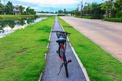 Красный круг велосипеда на траве в деревне сада Стоковое Фото