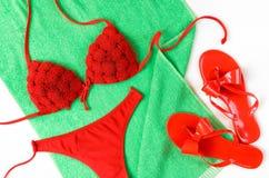 Красный купальный костюм и красные кувырки на зеленом полотенце Ткань лета Стоковые Изображения
