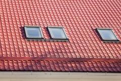 Красный металл крыл крышу с новыми Dormers, крышу Windows, окна в крыше и предохранение от черепицей крыши от снега BoardÑŽ стоковые изображения rf