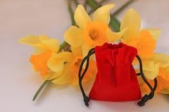 Красный мешок бархата с желтыми цветками на белой изолированной предпосылке стоковые изображения rf