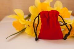 Красный мешок бархата с желтыми цветками на белой предпосылке, космос стоковая фотография