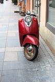 Красный мопед припаркованный около стены здания стоковые изображения