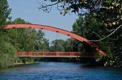 Красный мост удлиняя над рекой Стоковое Фото