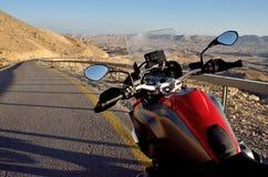 Красный мотоцикл на дороге в пустыне Негев около большого кратера, Израиля, Ближнего Востока стоковое фото
