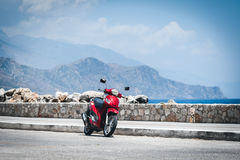Красный мотоцикл около береговой линии моря на городке Paleochora на острове Крита Стоковые Изображения