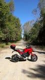 Красный мотоцикл приключения на грязной улице Стоковые Фото