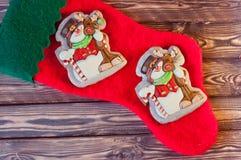 Красный носок рождества для подарков Санты кладя с славным пряником в форме снеговиков и оленей на деревянный стол Стоковая Фотография RF