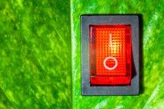 Красный переключатель мощности на зеленых листьях сохраняет ene мировоззренческой доктрины дружелюбное Стоковое Изображение RF