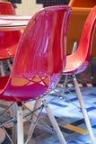 Красный пластичный стул вне дизайна звезды кафа отражая в мозаике пола стоковые изображения
