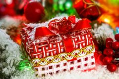 Красный подарок на рождество стоит на снеге против предпосылки шарика рождества и сияющей сусали накаляя света Bokeh Стоковые Фото