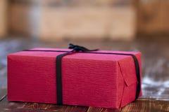 Красный подарок рождества украшенный с черными лентой и смычком на деревянном столе Стоковые Фото
