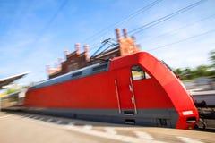 Красный поезд быстро проходя через вокзал Стоковое фото RF
