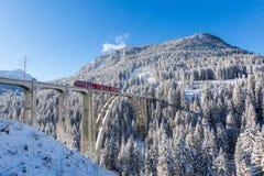 Красный поезд Rhaetian железнодорожный на виадуке Langwies, солнечности, зиме Стоковые Изображения