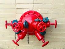 Красный пожарный гидрант со множественными соединениями на каменной стене стоковое изображение rf