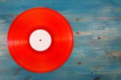 Красный показатель винила на голубой деревянной предпосылке Стоковая Фотография RF