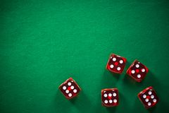 Красный покер dices на зеленом войлоке казино, предпосылке фары стоковое фото