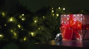 Красный подарок рождества с деревом на заднем плане стоковая фотография