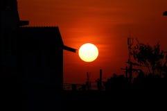 Красный полный заход солнца в доме города и предпосылке дерева Стоковая Фотография