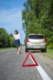 Красный предупредительный знак треугольника и женский водитель Стоковое фото RF