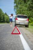 Красный предупредительный знак треугольника и сломленный автомобиль на дороге Стоковое Изображение