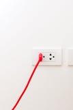 Красный провод с плоским штырем заткнул в гнездо Стоковое Фото