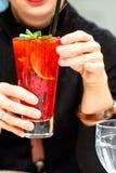 Красный прозрачный коктеиль с ягодами в руках девушек стоковые изображения rf