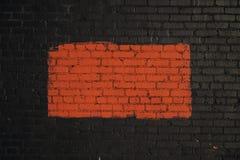 Красный прямоугольник покрашенный на черной кирпичной стене стоковое изображение rf
