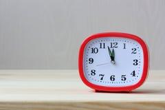 Красный прямоугольный пластиковый будильник на таблице стоковое изображение rf