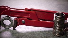 Красный разводной гаечный ключ metalwork для санитарных работ на фоне выключения воды и соединяясь выключения видеоматериал